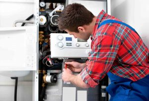 Plumber Servicing Gas Boiler